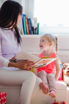 Woman reading book to charming girl