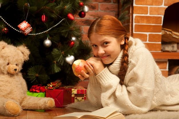 Woman reading book on christmas in front of tree