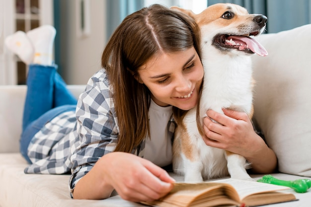 Woman reading book on couch with dog