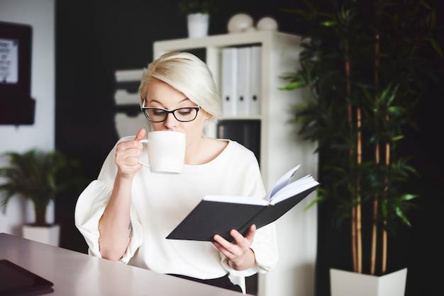Donna che legge un libro e beve caffè alla sua scrivania