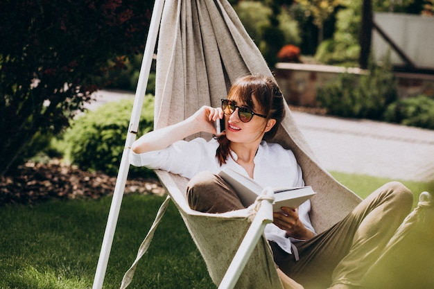 Woman reading a book in the garden by the house