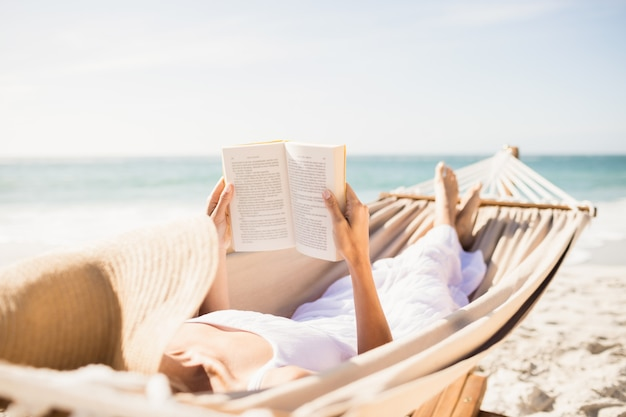 Woman reading book in hammock