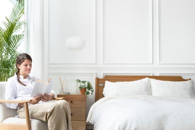Donna che legge un libro nella sua camera da letto
