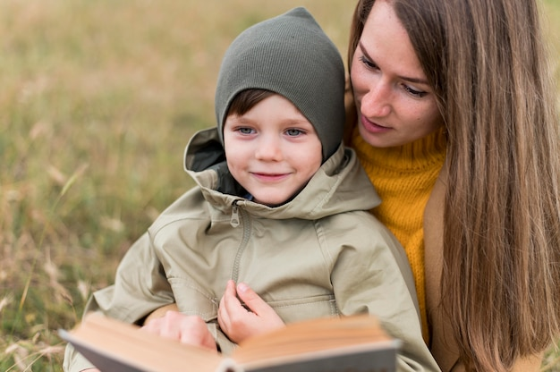Woman reading a book to his son