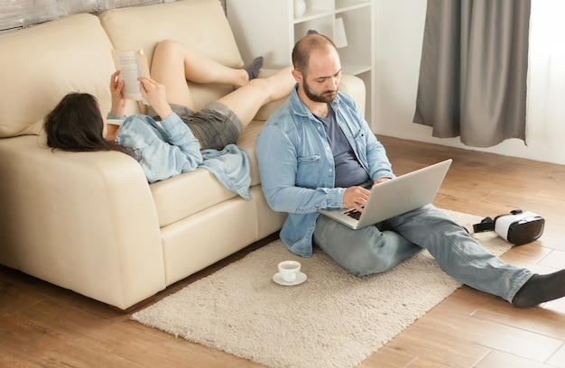 Donna che legge un libro sdraiata sul divano in soggiorno