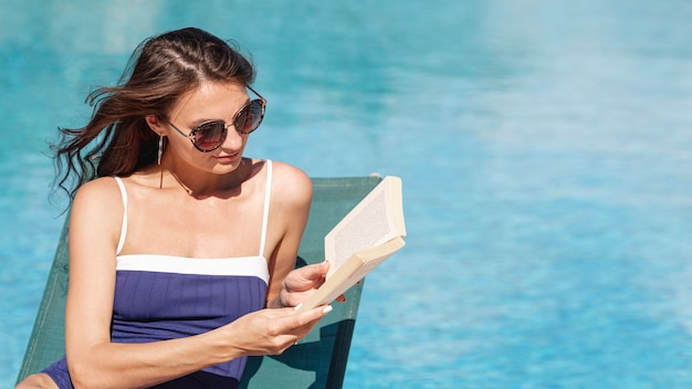 Woman reading book laying on sunbed