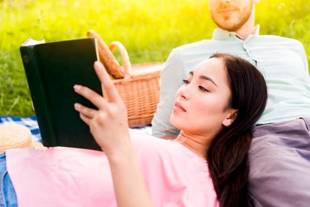 Woman reading book lying on boyfriends leg
