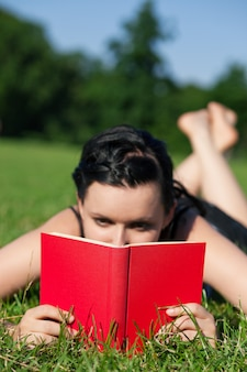 Woman reading book on meadow