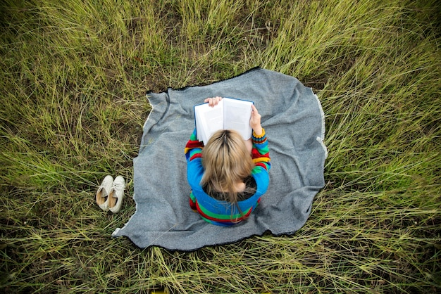 Woman reading book in the middle of a field