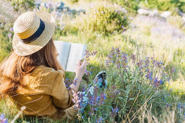 Woman reading a book in nature surrounded by vegetation and flowers