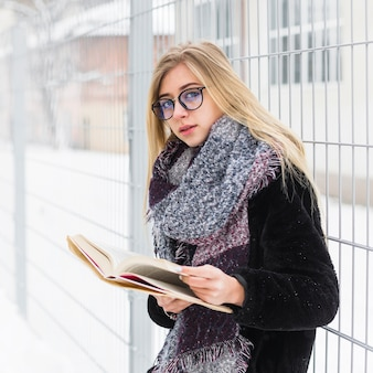 Woman reading book near fence on white street
