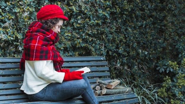 Woman reading book near firewood