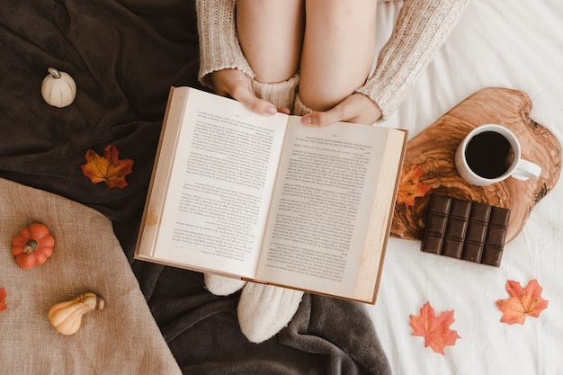 Woman reading book near snack and autumn symbols