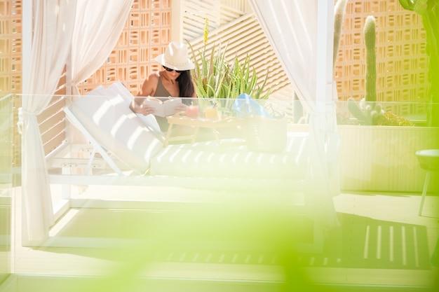 Женщина, читающая книгу на кровати с балдахином летом
