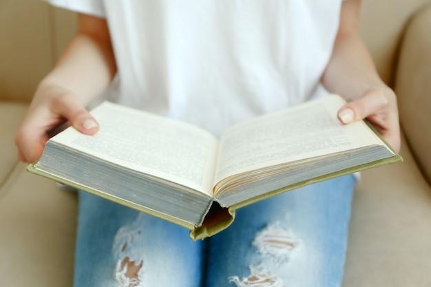 소파에 여자 읽기 책을 닫습니다.