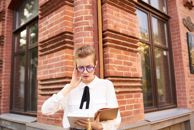 Женщина читает книгу на улице возле кирпичного здания и записной книжки, студент науки образования