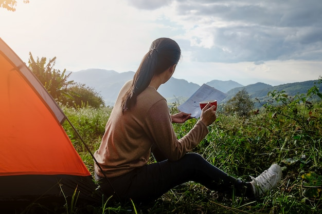 Woman reading a book outside the tent with morning sunlight at the morning. camping in forest. relax concept
