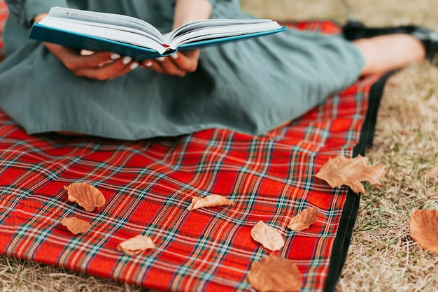 Woman reading a book on a picnic blanket