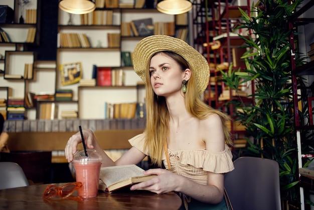 Женщина, читающая книгу, расслабляющаяся в кафе пить образ жизни. фото высокого качества