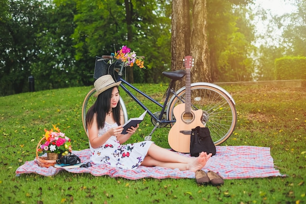 Woman reading a book on relaxing of time.asian lady have picnic in public park on vacation