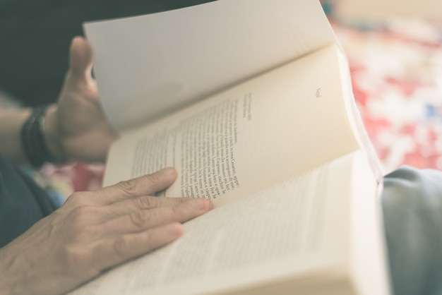 Woman reading book. selective focus, close up. cross processed with vintage film effect. warm toned.
