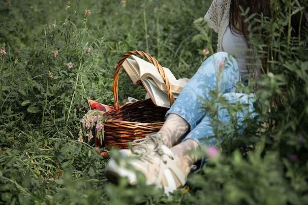Женщина, читающая книгу, сидя в саду