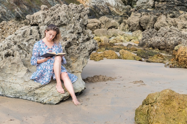 Woman reading a book sitting on a rock on the beach
