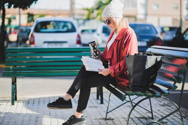 Woman reading book on street