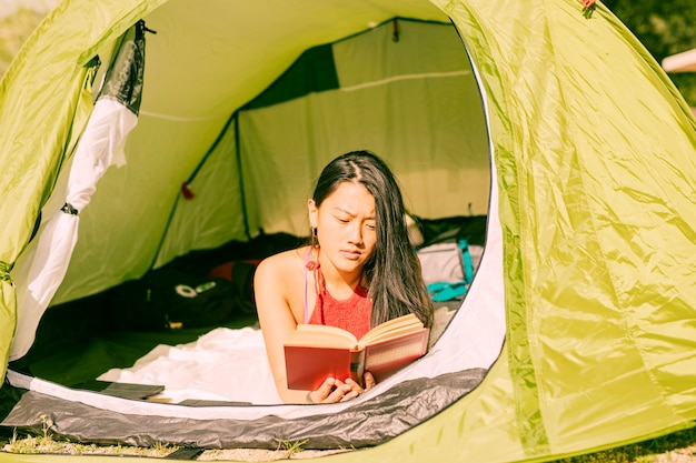 Woman reading book in tent