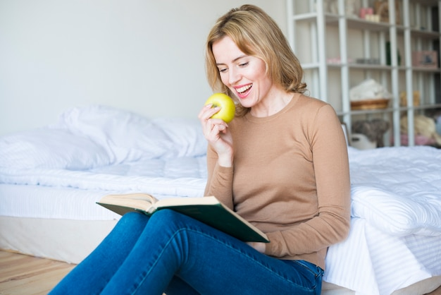 Woman reading book while eating apple