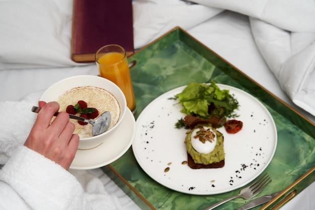 Женщина, читающая книгу во время завтрака в постели. женщина в халате за завтраком в постели отеля, крупным планом