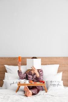 Женщина читает книгу во время вкусного завтрака в постели
