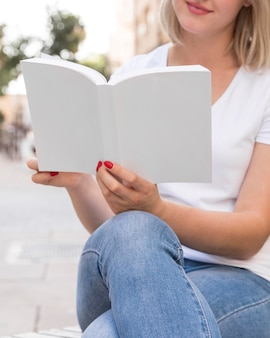 Woman reading book while sitting on bench outdoors