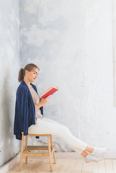 Woman reading book while sitting on stool at home