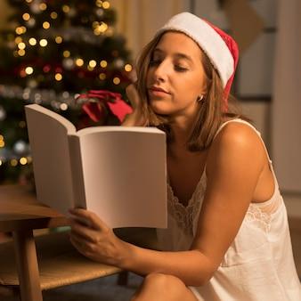 Donna che legge un libro mentre indossa il cappello della santa a natale