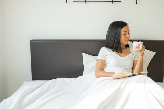Woman reading book with cup of coffee at home in the bedroom.
