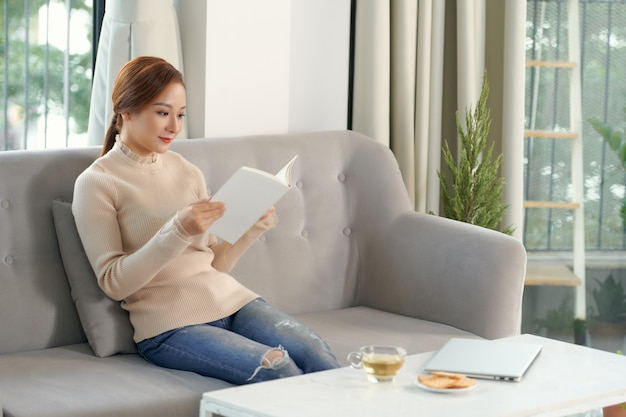Woman reading book with cup of tea at home in the living room