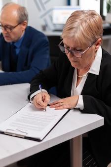그것을 서명하기 전에 회의실에서 금융 문서를 읽는 여자