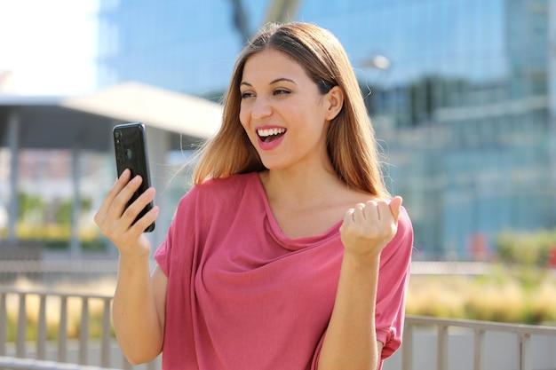 通りでスマートフォンでオンラインで良いニュースを読んでいる女性