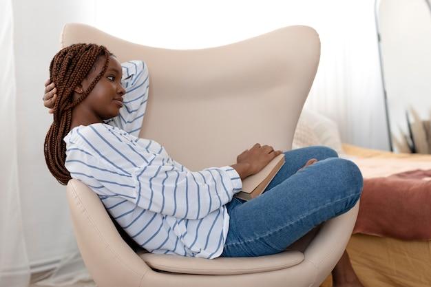 Donna che legge a casa inquadratura intera