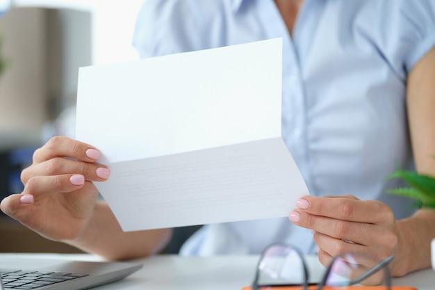 열린 봉투 사업가와 함께 테이블에 앉아 있는 동안 편지를 읽는 여성