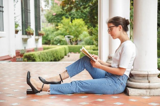 Женщина читает литературу в саду