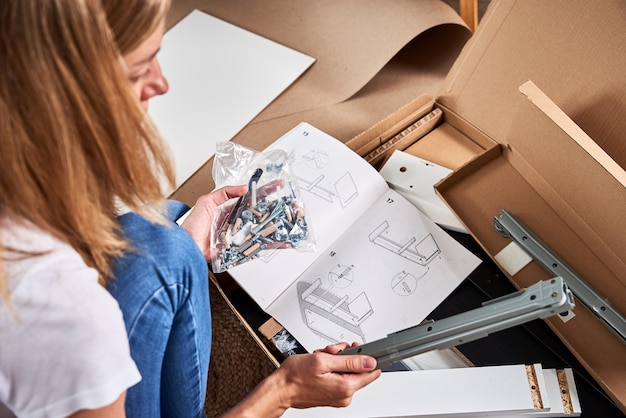 Woman reading manual instruction to assemble furniture