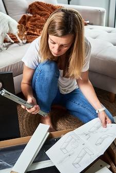 居間で家具を組み立てるためのマニュアルの指示を読んでいる女性