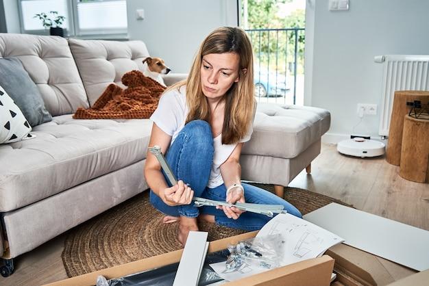 家具を組み立てるためのマニュアルの指示を読んでいる女性