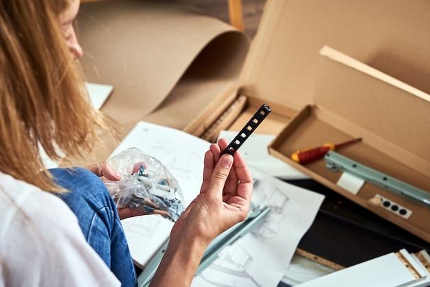 Женщина, читающая инструкцию по сборке мебели