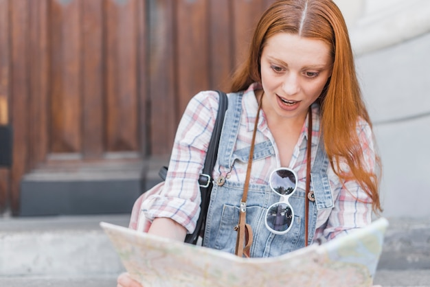 Woman reading map with surprise