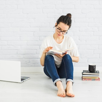 Woman reading near laptop and cup