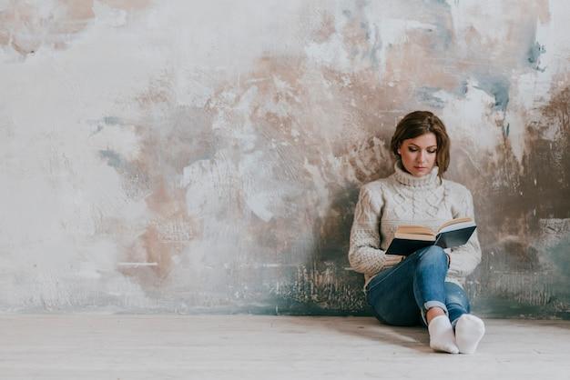 壁の近くで読書をする女性