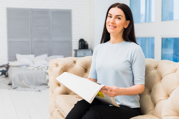Woman reading newspaper on couch